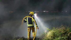 Bomberos de Orihuela evitan la propagación de un incendio de matorral entre una acequia y un chalet